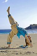 MR Yoga teacher and artist Lena Tancredi, doing yoga on a peaceful beach of Ibiza, Spain
