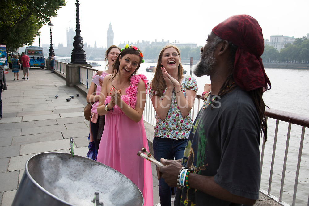 Bride to be Polly having fun with friends on the Southbank for her hen party. The group have a list of activities they have to tick off a list. Playing the steel drums. The The South Bank is a significant arts and entertainment district, and home to an endless list of activities for Londoners, visitors and tourists alike.