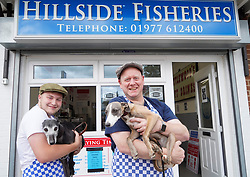 © Licensed to London News Pictures. 29/07/20. Ackworth, UK. Charlie Tipton, owner of Hillside Fisheries chip shop in Ackworth, West Yorkshire is offering free fish and chips to anyone who arrives wearing a flat cap and is accompanied by their pet whippet on Yorkshire Day on  Saturday August 1st. <br />Charlie is pictured with co worker  Jonny Chapman and whippets Misty and Gyp. <br />Yorkshire Day was set up in 1975 by the Yorkshire Ridings Society to celebrate and promote Yorkshire culture. <br />Picture Credit: Scott Merrylees/LNP