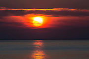 Clouds light up from the sun setting which is reflected in the calm waves of The English Channel from Folkestone Kent, England, United Kingdom.