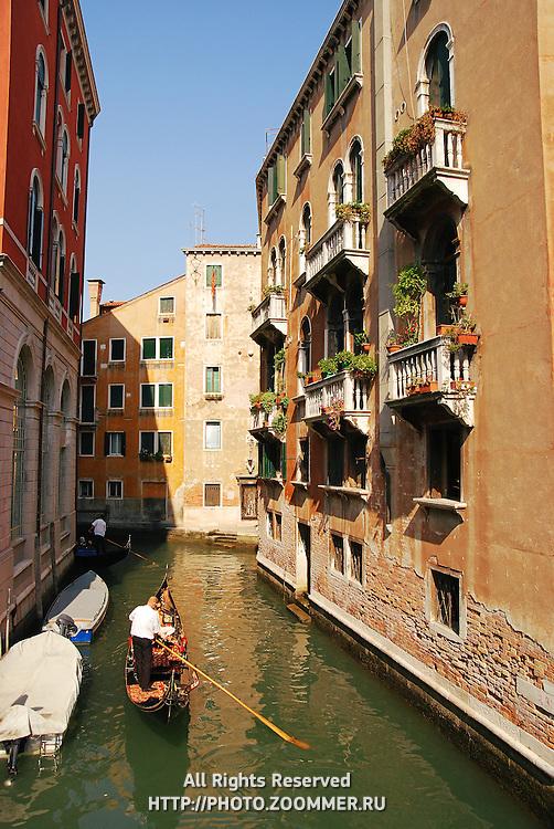 Gondola in venetian canal between buildings