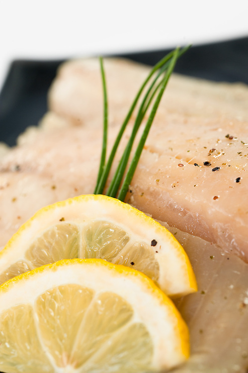Steamed tilapia with lemon slices and chive garnish
