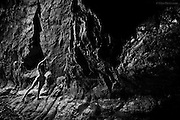 Faults within faults, shadows form in darkness. The nude woman gently tests her footing on the slippery rock at the base of the cave, gripping hard edges to steady herself as she moves further into the vast wet chamber. Over millennia the force of the sea has exposed, pummelled and forced open the soft veins of this ancient stone but amazingly, in what seems almost perpetual night, life clings to the ribbed surfaces far inside. Sounds of the day are muffled, save for the relentless roar of the waves at low tide. It's cool in here and the woman shivers in the damp air, her skin and muscles taut, her senses heightened to the strange environment. <br /> <br /> In a moment she finds herself wading through a deep, smooth-bottomed pool and she inhales sharply as the water pushes between her open thighs. The water shallows and she feels painful hard pebbles and small boulders beneath her delicate feet. She is almost invisible now and only the crunching sound of the shingle reveals her location.  Then there is silence for a short while. As my eyes adjust, a gentle prick of light pierces the darkness beyond and gradually becomes more distinct. I now realise this is not just a cave it's a tunnel. Across the small circle of light moves the slender silhouette of the woman and in a blink of the eye she was gone.