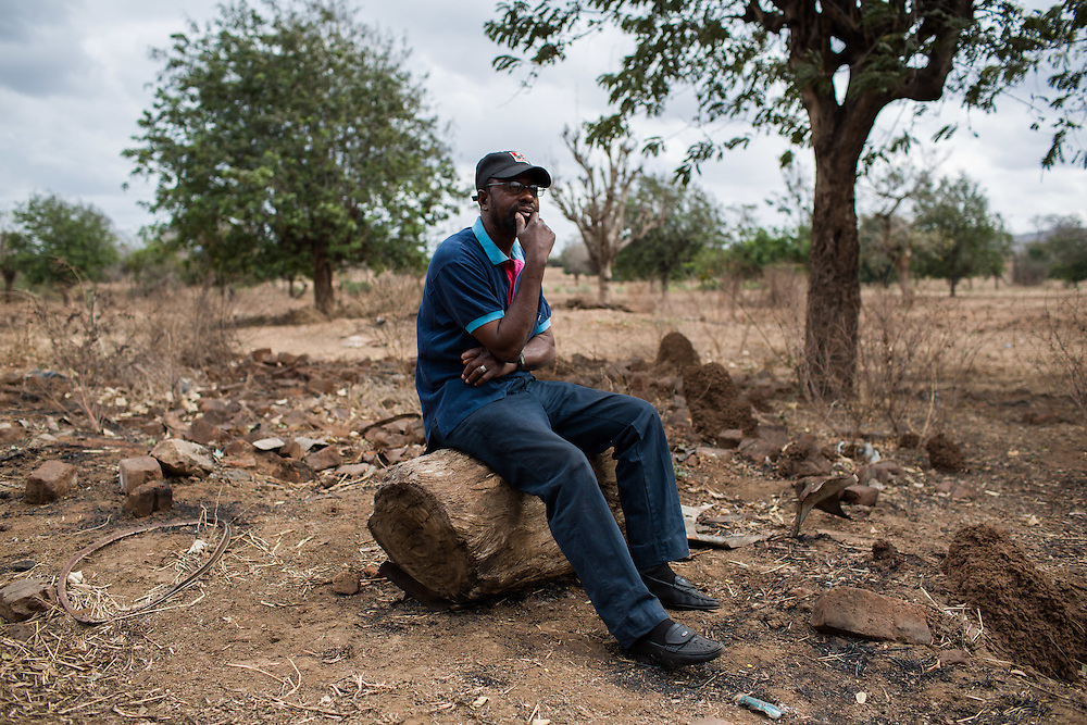 Chipanga, Tete Province, Mozambique. Armando Saize sits in the remains of his demolished house. He, along with over 700 other families from four villages, was resettled to 25 do Septembro to make way for the exploitation of coal in the Moatize region by Brazilian energy company Vale.