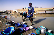 Two local girls washing dishes in the Niger River. Kouakourou, Mali. (Supporting image from the project Hungry Planet: What the World Eats.)