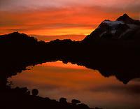 Mt. Shuksan, WA, USA  9,127 ft..Mt. Shuksan in North Cascades National Park..Sunrise reflection in pond from Mt. Baker Wilderness..Brett Baunton