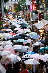 Many umbrells in rain in trendy Takeshita Street in Harajuku Tokyo