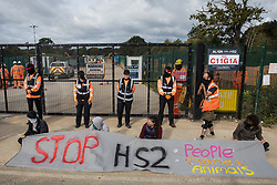 Environmental activists from HS2 Rebellion sit behind a banner to block a gate providing access to a site for the HS2 high-speed rail link on 12 September 2020 in Harefield, United Kingdom. Anti-HS2 activists continue to try to prevent or delay works on the controversial £106bn HS2 high-speed rail link in the Colne Valley where thousands of trees have already been felled.