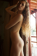 Nude woman with long hair standing in doorway and looking provocatively at the camera