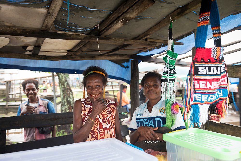 Two women, one with a bilum hanging from her head, smile at the market in Vanimo Papua New Guinea (2017)