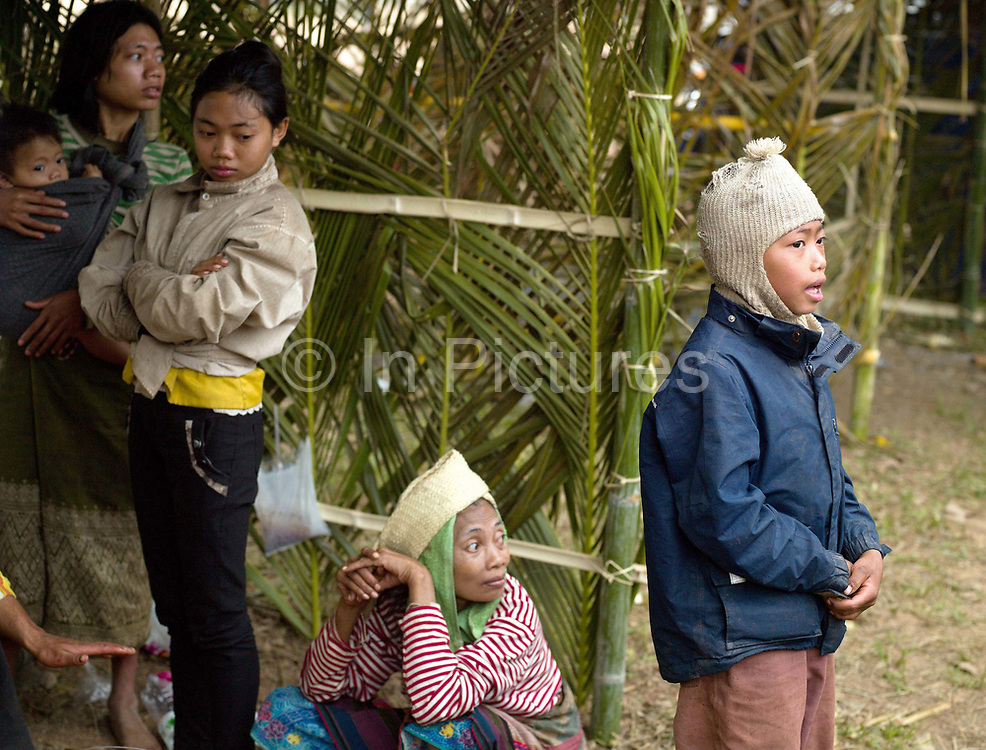 A Yumbri family set up an example hut made from bamboo, coconut and banana leaves and sing traditional songs at the Sayaboury elephant festival, Sayaboury province, Lao PDR and collect donations from the tourists at the festival. The Yumbri, otherwise known as Yellow Leaves, Tong Luang or Mlabri are the last remaining hunter-gatherer Austroasiatic-speaking community living in the primary forests and river basins of the Nam Poui region in Sayaboury province. They are Laos smallest ethnic group with estimates of the numbers of Yumbri remaining varying between 21 and 30 individuals.