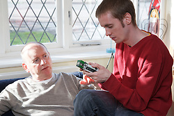 Young man with autism and his father, playing with toy bendy bus. Cleared for Mental Health issues.