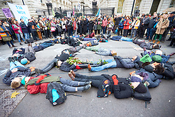 © Licensed to London News Pictures. 24/11/2018. LONDON, UK.  Protesters from Extinction Rebellion lie in the road forming an hourglass symbol  as part of a Memorial March and an ongoing campaign of civil disobedience to highlight the urgency of action on climate change and species loss.  Photo credit: Cliff Hide/LNP