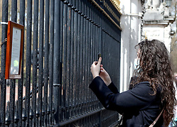 A woman takes a picture of the announcement of the death of the Duke of Edinburgh, who has died at the age of 99, hung on the gates of Buckingham Palace, London. Picture date: Friday April 9, 2021.