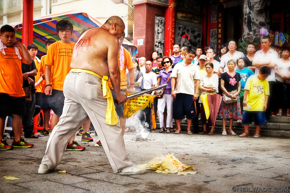 This man is performing a Ji Tong ritual.  The spirit-medium, said to be possessed by the spirit of a Taoist God, self-flagellates at a religious ceremony in Tainan, Taiwan.  The blood on his back is from repeated blows from various sharp weapons.