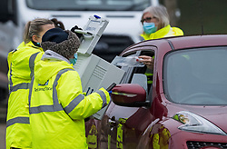 © Licensed to London News Pictures. 01/02/2021. Woking, UK. A members of the public places a COVID-19 test in to a container at a drive through COVID-19 test centre in Goldsworth Park in Woking, Surrey, where a South African variant of Covid-19 has been found. Photo credit: Ben Cawthra/LNP
