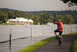 © Licensed to London News Pictures. 09/08/2021. Henley-on-Thames, UK. A man rides his bike along the river bank, ahead of the the Henley Royal Regatta which starts on Wednesday, set on the River Thames by the town of Henley-on-Thames in Oxfordshire, England. Established in 1839, the five day international rowing event, raced over a course of 2,112 meters (1 mile 550 yards), is considered an important part of the English social season. Photo credit: Ben Cawthra/LNP