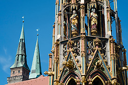 Schoene Brunnen (Beautiful Fountain) and spires of St Sebald's church in Nuremberg in Bavaria Germany