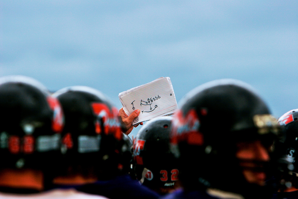 During the last practice before the homecoming game, a diagram of a key play is hoisted for the sqaud to review.