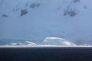 Sunlit iceberg infront of mountainous cliffs of Brabant Island, Gerlache Strait. First land sighted after crossing Drake Passage on the Kapitan Khlebnikov's Epic Antarctic Voyage Dec 2009 - Jan 2010.