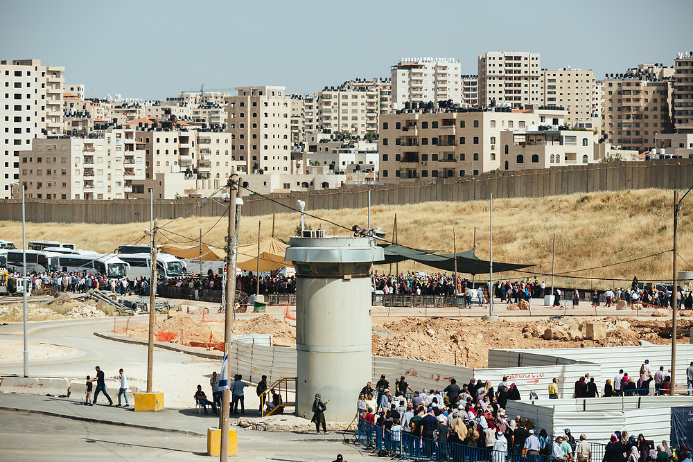 Houses at the Qalandiya refugee camp and a section of Israel's separation wall are seen in the background, as Palestinians cross Qalandiya checkpoint, south of Ramallah, West Bank, on May 17, 2019, on their way to perform the second Friday Prayer of the Muslim holy month of Ramadan, at the Al Aqsa Mosque in Jerusalem. Israeli authorities are introducing biometric border crossing systems at West Bank checkpoints, thus minimizing the interaction between Israeli soldiers and Palestinians crossing into Israel.