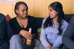 Two teenage girls drinking alcohol and smiling,