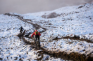 Riders cut through the mud and snow on the way down stage three of the Kinlochleven Enduro.