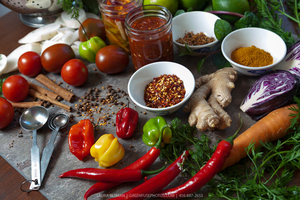 A variety of fresh produce and spices and kitchen tools laid out on cutting boards for the preparation of Harissa and Asian-styled pickles: fresh chili peppers, coriander seeds, ginger, dried peppers, tomatoes, cinnamon sticks, limes, carrots, purple cabbage, diakon radish, lemon grass oil, Malabar spinach.