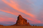 """Shiprock, a prominent peak located northwestern New Mexico, is framed by cirrus clouds at sunrise. The peak rises 1,583 ft (482 m) above the surrounding landscape and has a total elevation of 7,177 ft (2,188 m). The peak is located on Navajo tribal land and is sacred to them. The Navajo name for the peak is Tsé Bit'a'í, which means """"rock with wings."""" Tribal legend says a great bird brought the Navajo people from the North to the present-day Four Corners area."""