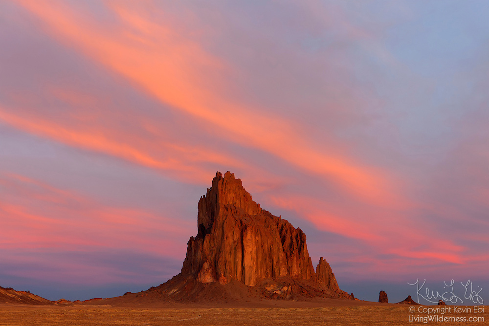 "Shiprock, a prominent peak located northwestern New Mexico, is framed by cirrus clouds at sunrise. The peak rises 1,583 ft (482 m) above the surrounding landscape and has a total elevation of 7,177 ft (2,188 m). The peak is located on Navajo tribal land and is sacred to them. The Navajo name for the peak is Tsé Bit'a'í, which means ""rock with wings."" Tribal legend says a great bird brought the Navajo people from the North to the present-day Four Corners area."