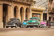 Vintage cars on street between buildings, Paseo de Marti, Havana, Cuba