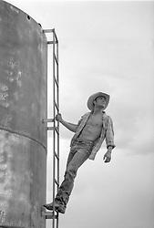 cowboy climbing up a water tower