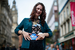 © Licensed to London News Pictures. 18/09/2014. Glasgow, UK. A women putting a 'Yes' sticker on whilst people of Scotland going to polling stations in Glasgow to vote on the Scottish independence referendum on Thursday, 18 September 2014. Photo credit : Tolga Akmen/LNP