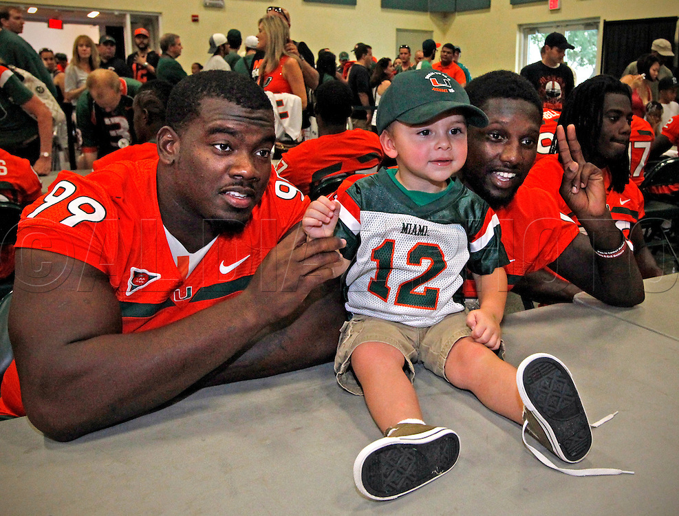 Marcus Forston and Jacory Harris pose for pictures with fan Aiden Leone, 2, of Kendall during CanesFest  for the University of Miami Football team on Campus in Coral Gables on August 27, 2011.