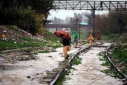 A school boy crosses a waterlogged railway track after heavy rain in northwest Pakistan's Peshawar, Feb. 25, 2015. At least two women were killed as a roof of a house collapsed in Peshawar. Heavy rains have wreaked havoc in different areas of Kashmir, Khyber Pakhtunkhwa and Gilgit-Baltistan on Wednesday, local media reported. EXPA Pictures © 2015, PhotoCredit: EXPA/ Photoshot/ Umar Qayyum<br /> <br /> *****ATTENTION - for AUT, SLO, CRO, SRB, BIH, MAZ only*****