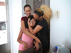 Nerys Medina hugs her daughters Glennys (left) and Karelys, at their home in the town of San Lorenzo as they package to leave Puerto Rico on October 2. After deciding against their will to leave since their house got damaged, her husband Carlos Rolâ¤â€n, a financial planner is jobless and their daughters' schools are closed for an unknown amount of time forcing many Puerto Ricans to fly to the U.S. after Hurricane Maria, (category 4) passed through Puerto Rico devastating the island leaving residents without power and ways to communicate on Sept. 20. on October 02, 2017. Photo by Pedro Portal/Miami Herald/TNS/ABACAPRESS.COM