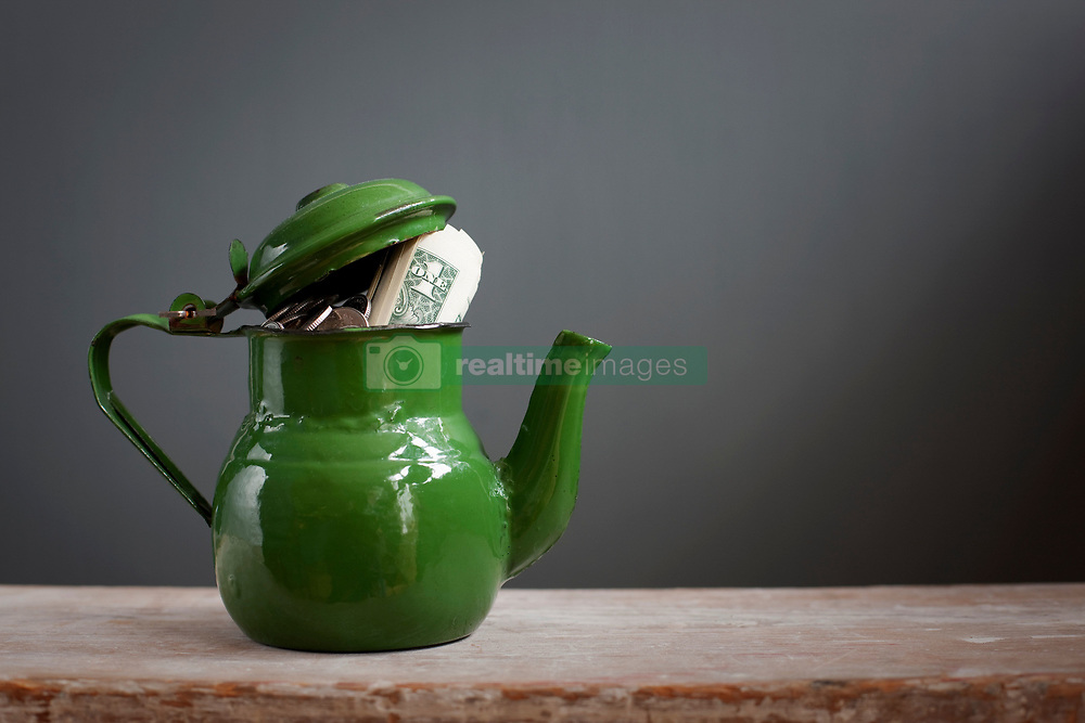 Teapot with dollar notes inside (Credit Image: © Image Source/Ian Nolan/Image Source/ZUMAPRESS.com)