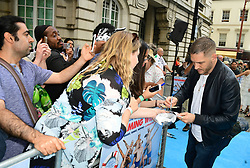 Tom Hardy signs autographs for fans during the Swimming with Men premiere held at Curzon Mayfair, London.