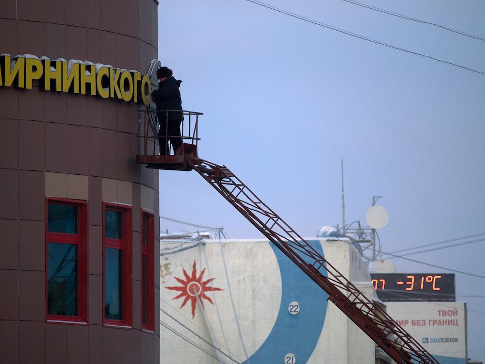 """Ein Arbeiter reinigt den Schriftzug des Hotels """"Polar Star"""" vom Schnee. Dies von einem Kranwagen aus bei einer Temperatur von -31 Grad Celsius in der sibirischen Stadt Jakutsk. Die Temperaturen sind derzeit noch recht mild und es kann bis zu -50 Grad Celsius in Jakutsk werden.<br /> <br /> Worker cleaning a sign of the Polar Hotel in Yakutsk from snow. Yakutsk is a city in the Russian Far East, located about 4 degrees (450 km) below the Arctic Circle. It is the capital of the Sakha (Yakutia) Republic (formerly the Yakut Autonomous Soviet Socialist Republic), Russia and a major port on the Lena River. Yakutsk is one of the coldest cities on earth, with winter temperatures averaging -40.9 degrees Celsius."""