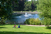 People sitting relaxing on sunny day by water fountain pond in Christchurch Park, Ipswich, Suffolk, England, UK