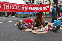A woman prepares her placard ahead of yet more direct action as hundreds of environmental protesters from Extinction Rebellion occupy Marble Arch, camping in the square and even on the streets, blocking access to traffic on Park Lane and Oxford Street in London's usually traffic-heavy west end. . London, April 16 2019.