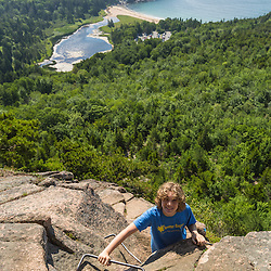 A teenage boy hiking on The Beehive in Maine's Acadia National Park.