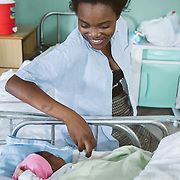 INDIVIDUAL(S) PHOTOGRAPHED: . LOCATION: St. Damien Hospital, Nos Petits Frères et Sœurs, Tabarre 41 Commune, Haïti. CAPTION: Grinning happily, Fessiva Lamour reaches towards her sweet baby Jessica.