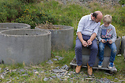 A father and son look at a smartphone together during a day out in wales, sit on concrete blocks.