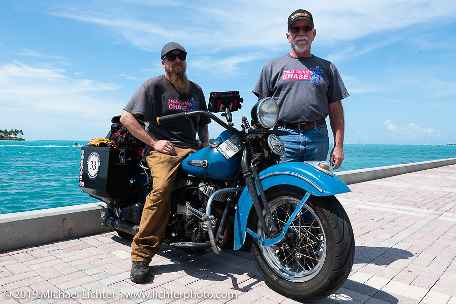 Kyle Rose with his Dad (and CCC sweep truck driver) John at the end of the Cross Country Chase motorcycle endurance run from Sault Sainte Marie, MI to Key West, FL. (for vintage bikes from 1930-1948). The Grand Finish in Key West's Mallory Square after the 110 mile Stage-10 ride from Miami to Key West, FL and after covering 2,368 miles of the Cross Country Chase. Sunday, September 15, 2019. Photography ©2019 Michael Lichter.