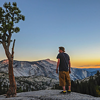 A hiker admires the view from Olmstead Point, a famous scenic turnout on the Tioga Pass Road through Yosemite National Park, California.  Behind are Tenaya Canyon, Cloud's Rest and Half Dome.