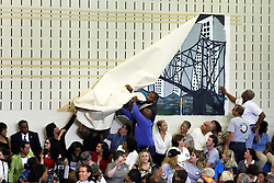 27 August 2015. Andrew P. Sanchez & Copelin-Byrd Multi Service Center, Lower 9th Ward, New Orleans, Louisiana.<br /> A large canvas mural falls off the wall moments before President Barack Obama speaks. <br /> Photo credit©; Charlie Varley/varleypix.com.