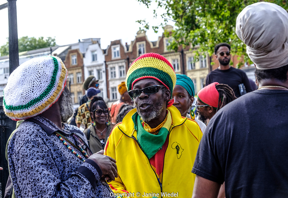 Chatting and enjoying Groundation music at annual Reparations Rebellion event on Afrikan Emancipation Day in Windrush Square Brixton 2021.