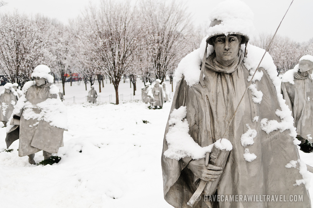"""The Korean War Memorial on the National Mall on a snowy winter morning after fresh snow. The Korean War Veterans Memorial, unveiled in 1992, sits on the northwestern end of the National Mall, not far from the Lincoln Memorial. It consists of several elements designed by different people and groups. It has a triangular footprint with the main elements being """"The Column"""" consisting of 19 stainless steel solders, each over 7 feet tall, and a reflective granite wall etched with the faces of thousands of Americans who lost their lives in the war. At one end of the triangle, behind the soldiers, is a grove of trees. At the other is a large American flag and a small Pool of Remembrance. Among the designers were Frank Gaylord (the soldiers) and Louis Nelson (the reflecting granite wall)."""