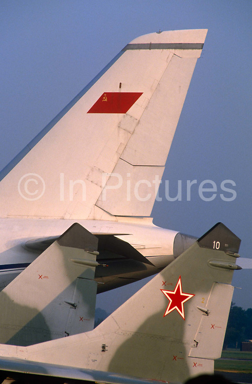 "The tails of a The Mikoyan MiG-29 (Fulcrum) fighter jet and an Antonov An-124 Ruslan transporter are seen visiting the 1988 Farnborough Air Show. The insignia of the era, a red star and hammer and sickle are clearly seen on the aircraft, just over a year before the collapse of Communism with the fall of the Berlin Wall. The Mikoyan MiG-29 or ""Fulcrum"" is a fourth-generation jet fighter aircraft designed in the Soviet Union for an air superiority role. Developed in the 1970s by the Mikoyan design bureau, it entered service with the Soviet Air Force in 1983, and remains in use by the Russian Air Force as well as in many other nations."